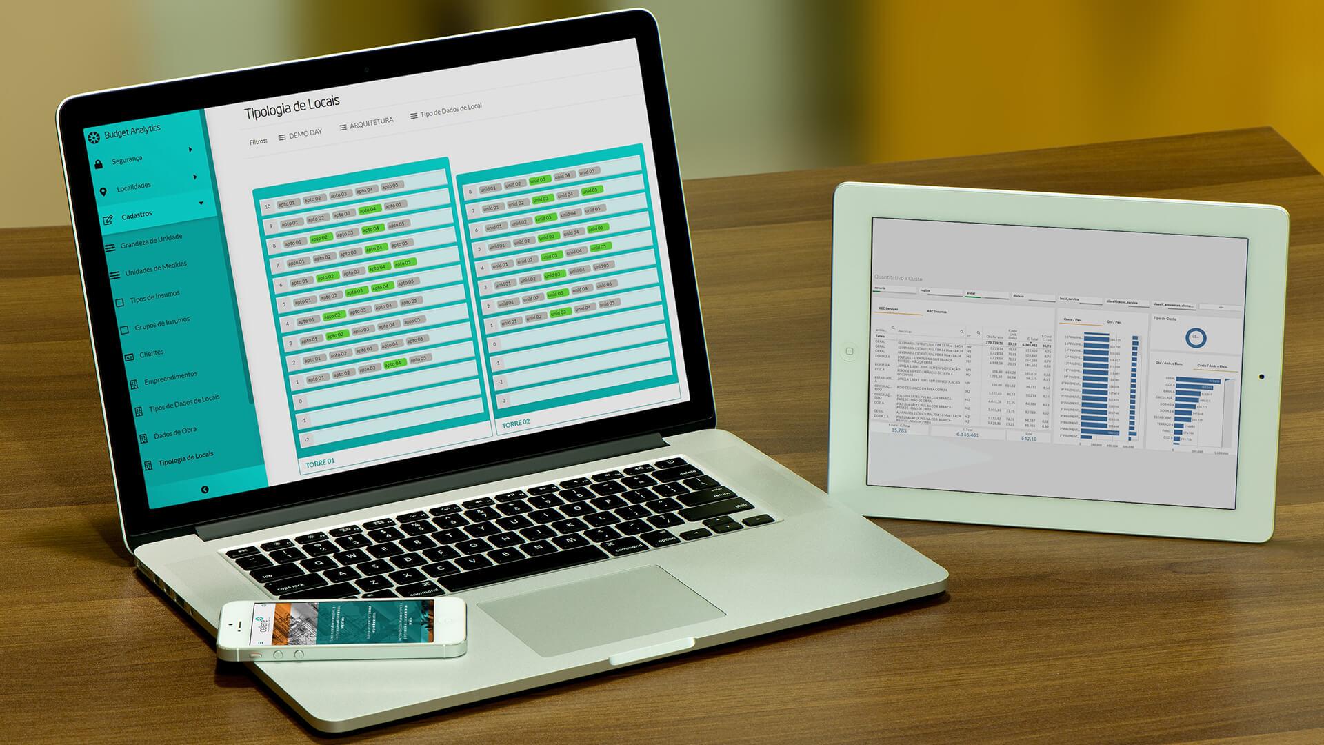 notebook em cima de uma mesa de madeira, com um sistema de gestão de obra aberto