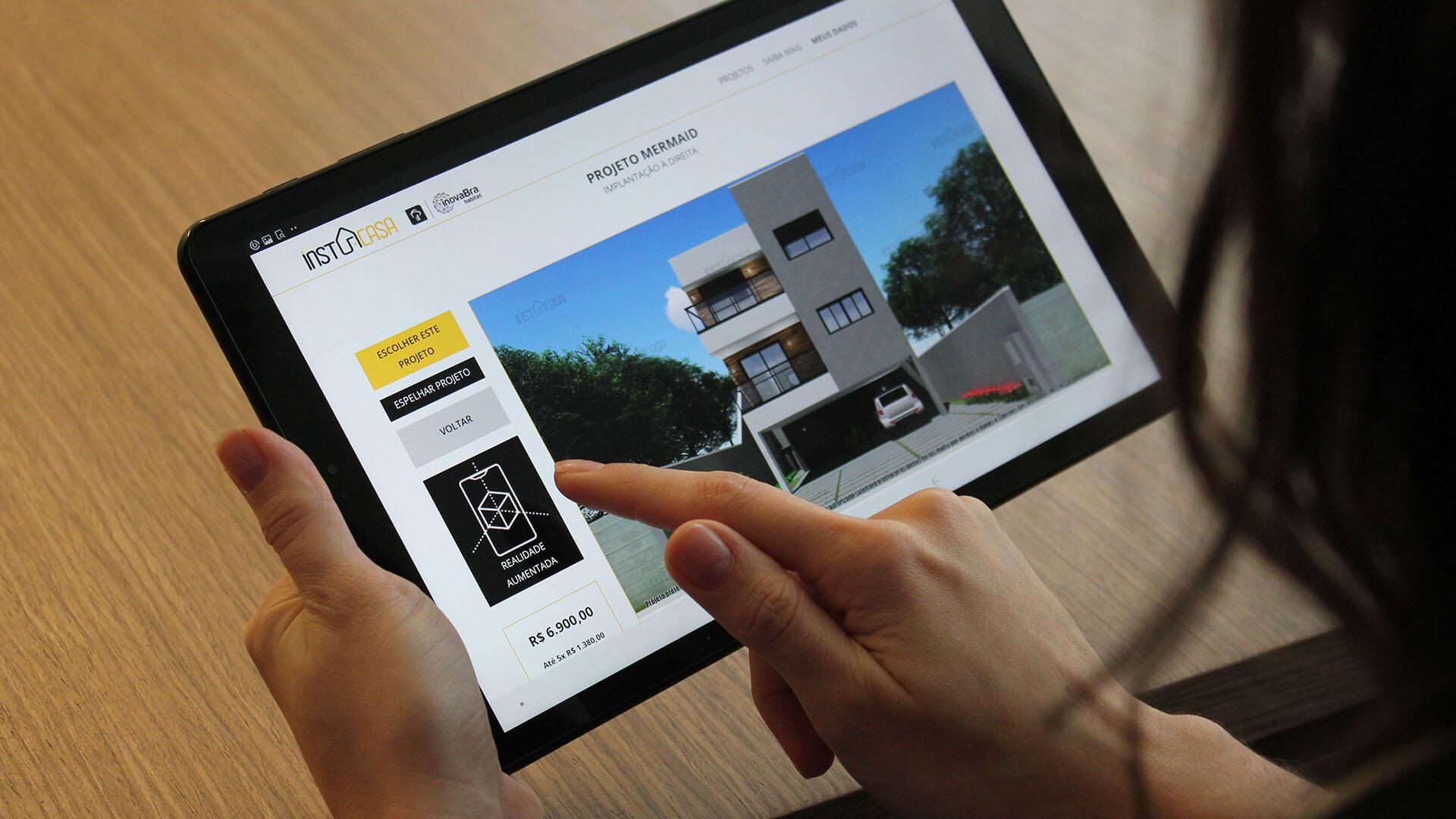 mãos segurando um tablet com o aplicativo da instacasa aberto